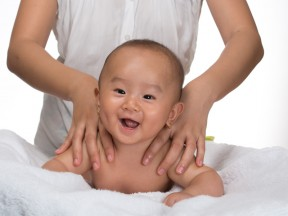 Laughing baby getting massage
